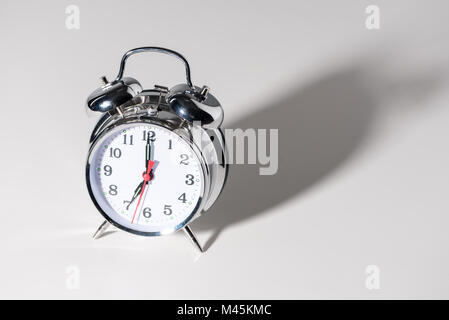 close-up view of shiny alarm clock with shadow on grey - Stock Photo