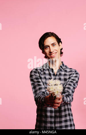Sweet guy in checkered shirt holding and offering bouquet of white flowers - Stock Photo