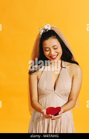 Asian bride in beige wedding dress holding a red heart isolated on orange - Stock Photo