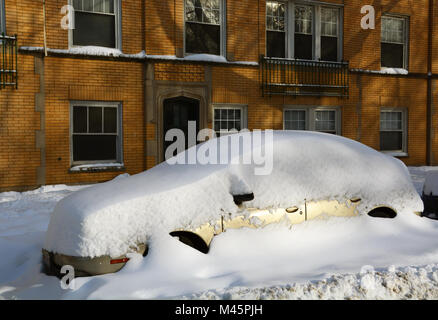 A car is buried in the snow on a residential side street after a series of snow storms in Chicago. - Stock Photo