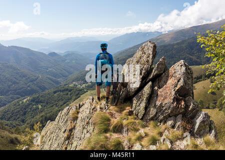 E-Mountainbiker enjoys the view from a mountain above Bogno,Ticino,Switzerland - Stock Photo