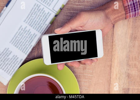 Man using smart phone by coffee and newspaper on table - Stock Photo