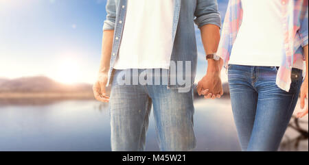 Composite image of hip young couple holding hands - Stock Photo