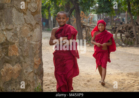 Young monk boys walking in a small town outside Bagan Myanmar - Stock Photo