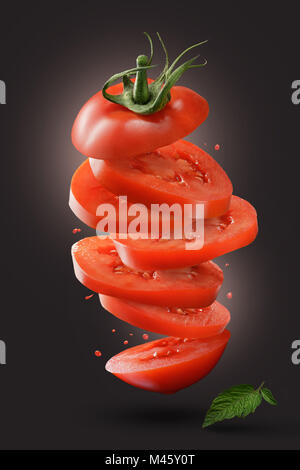 sliced flying tomato with green leaf on black - Stock Photo