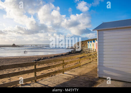 Traditional English beach huts above the beach in Cornwall. - Stock Photo