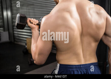 Rear view of shirtless man lifting heavy dumbbells - Stock Photo