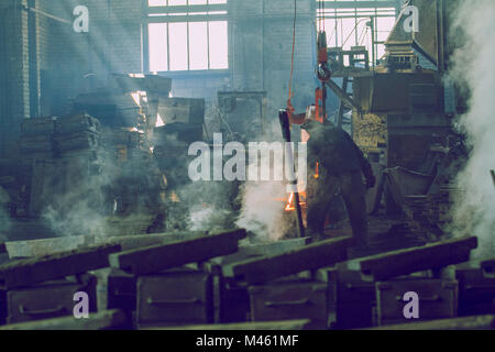 Cesis, Latvia, Metal foundry, workers pour metal, factory in city Cesis 2011.