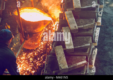 Cesis, Latvia, Metal foundry, workers pour metal, factory in city Cesis 2011. - Stock Photo