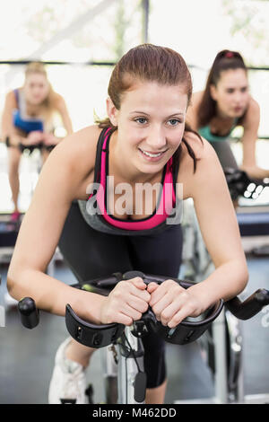 Fit group of people using exercise bike together - Stock Photo
