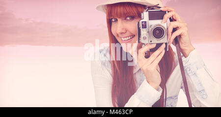 Composite image of attractive hipster photographing with camera - Stock Photo