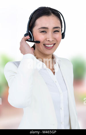 Composite image of smiling businesswoman using headset - Stock Photo