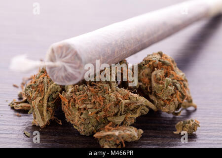 Close up of dried marijuana leaves and joint - Stock Photo