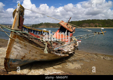 Frontal view of an old fishing boat turned on a side, wrecked and rotting on a rocky bank by the Mira River bank. - Stock Photo
