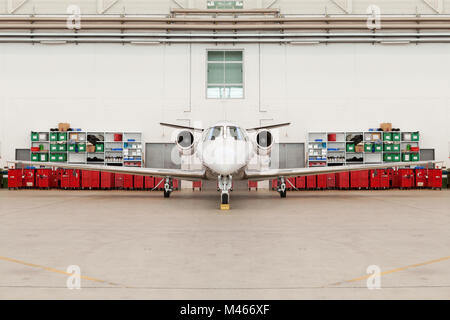 Front View of Small Airplane in Hangar - Stock Photo