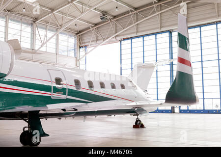 Small private corporate jet in a hangar - Stock Photo