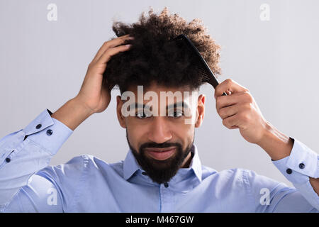 Portrait Of A Young Man Combing His Hair With Hair comb - Stock Photo