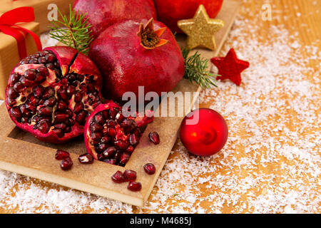 Fresh ripe pomegranates on wooden background and Christmas decoration. - Stock Photo