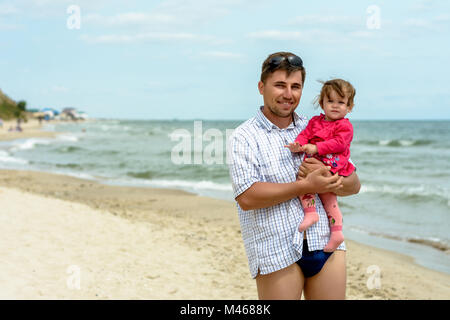 Young father in sunglasses on the beach with a little daughter - Stock Photo