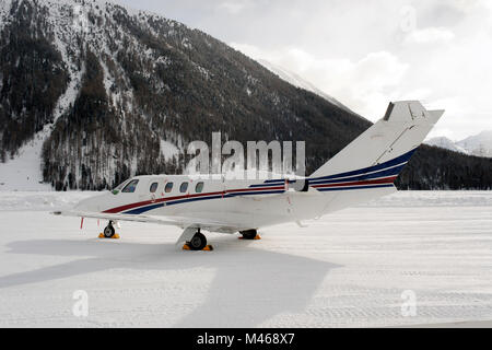 A private jet in the airport of St Moritz in the alps switzerland in winter - Stock Photo