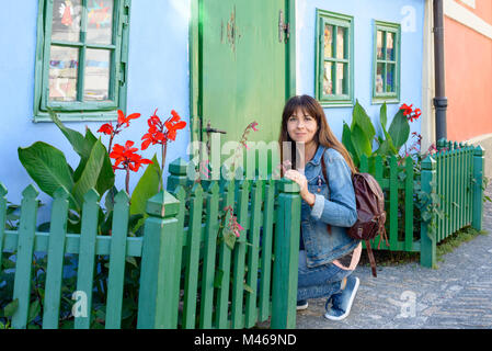 A girl posing in the Golden Lane, Czech  Zlata ulicka, is a street situated in Prague Castle, Czech Republic - Stock Photo