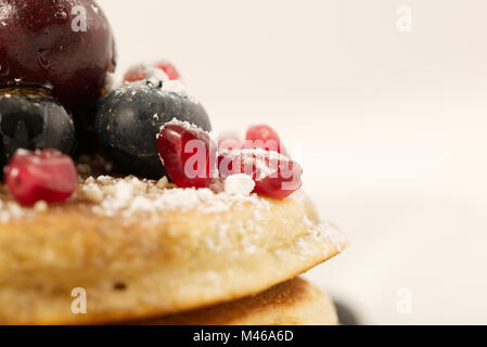 Breakfast pancakes topped with blueberries, cherries, pomegranate seeds and icing sugar (powdered sugar) and maple - Stock Photo
