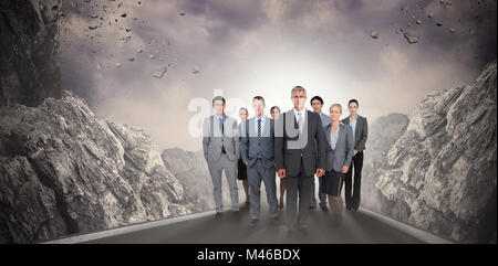 Composite image of smiling business team looking at camera - Stock Photo