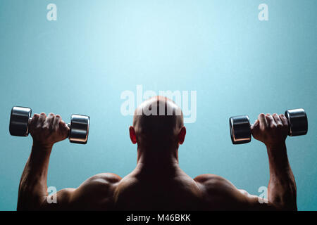 Composite image of rear view of muscular man lifting dumbbells - Stock Photo
