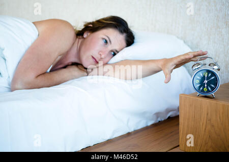 tired woman reaching out to turn off her alarm - Stock Photo