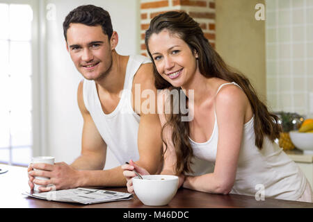 Young couple reading newspaper while having breakfast - Stock Photo