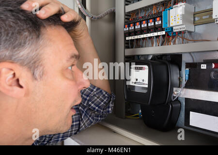 Close-up Of A Shocked Man Looking At Electricity Meter - Stock Photo