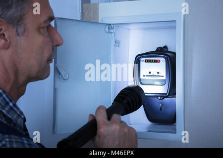 Close-up Of A Electrician Examining A Electricity Meter With A Torch - Stock Photo