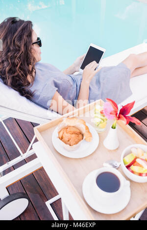 Young woman relaxing on a sun lounger near poolside - Stock Photo