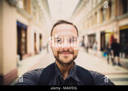 Portrait of a happy man with beard taking selfie. Hipster tourist smiles into the camera. Blurred background. - Stock Photo