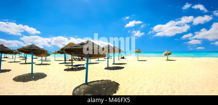 Panoramic landscape with sunshades on the sandy beach at sunny day. Nabeul, Tunisia, North Africa - Stock Photo