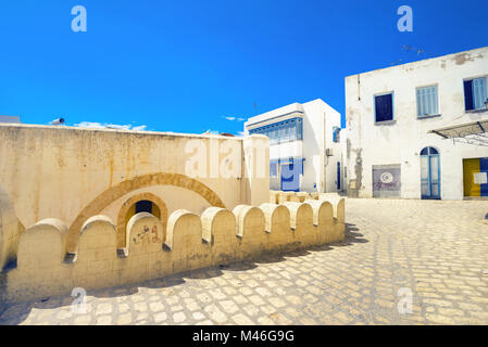 Street scene with part of fortress wall and white houses in Sousse. Tunisia, North Africa - Stock Photo