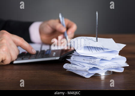 Close-up Of A Businessman Calculating Invoice Using Calculator At Wooden Desk - Stock Photo