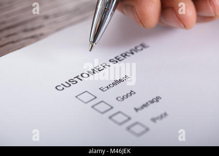 Close-up Of A Person Filling Customer Service Satisfaction Survey Form On Wooden Desk - Stock Photo