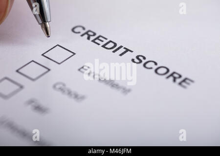 High Angle View A Person Filling Credit Score Form - Stock Photo