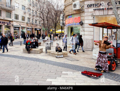 A violinist plays for tips at the busy corner of Ben Yehuda and Yafo Street in Jerusalem. - Stock Photo