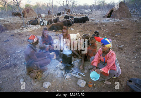 Namibia. Kaokoveld, near Opuwo. Himba tribe. Family at the fire place. Right: woman of Herero tribe with  typical - Stock Photo