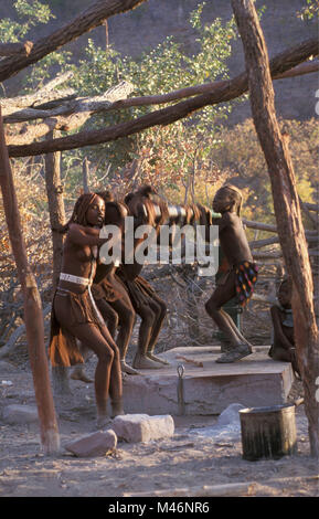 Namibia. Kaokoveld, near Opuwo. Himba tribe. Children pumping water. - Stock Photo