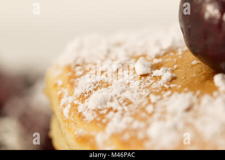 Breakfast pancakes topped with a cherry and icing sugar (powdered sugar) isolated on a white background. Breakfast - Stock Photo