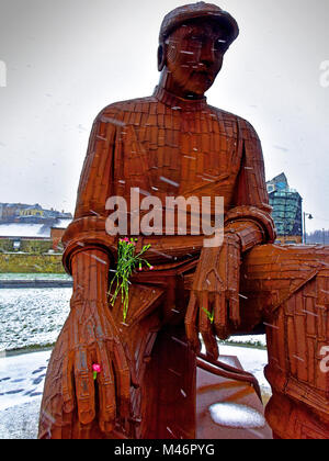 Fiddlers Green Fishermans statue in snow fall with flower - Stock Photo