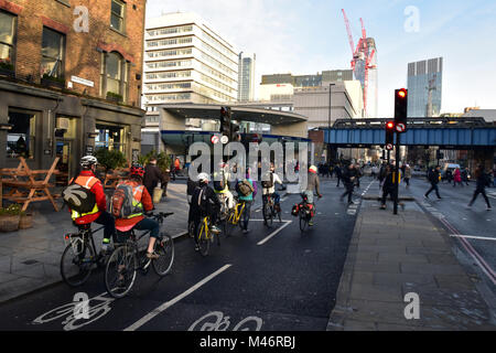 cyclists waiting at a red light at a road junction opposite to southwark tube station during the morning rush hour - Stock Photo