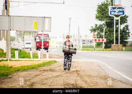 Krasnodar, Russia - June 1, 2017: Hitchhiking. Girl auto-stopper. The girl with the backpack stops the car. Voting - Stock Photo