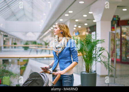 Young woman with baby during shopping - Stock Photo