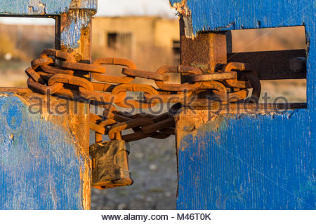 A padlock and a rusty metal chain securing access gates to derelict land on Morecambe sea front, formerly the site - Stock Photo
