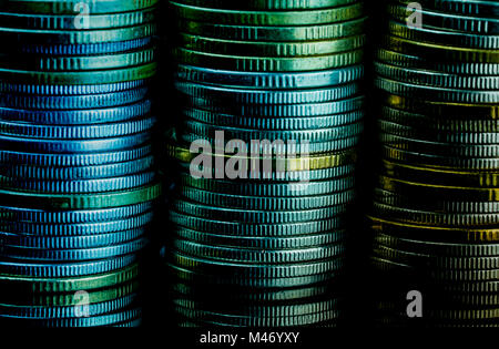 Macro shot detail of golden and silver color coin stacks on dark background with copy space for text. Business and finance growth, saving money, inves