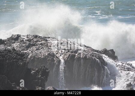 Waves crashing over rocks at Bonville Headland, Sawtell, NSW, Australia - Stock Photo